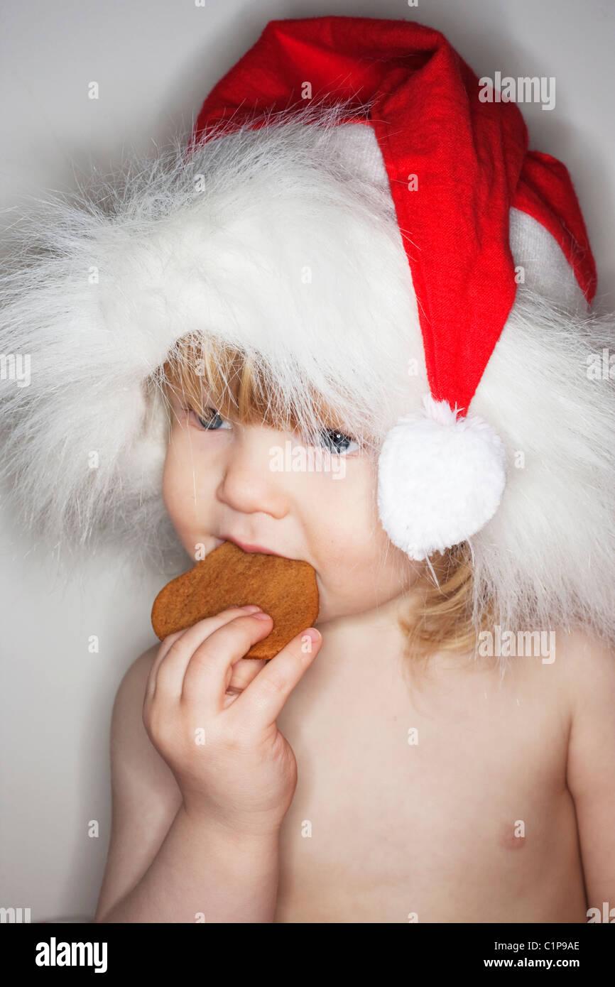 Boy wearing santa hat, eating biscuit - Stock Image