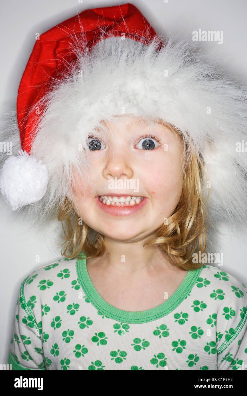 Studio portrait of girl wearing santa hat - Stock Image