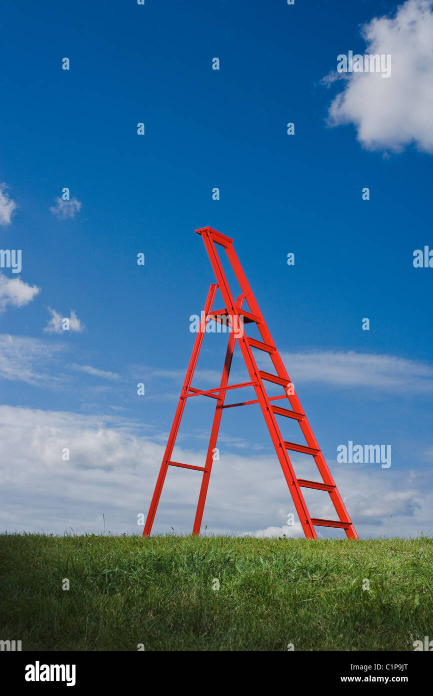 Red ladder in grass  field against blue sky - Stock Image