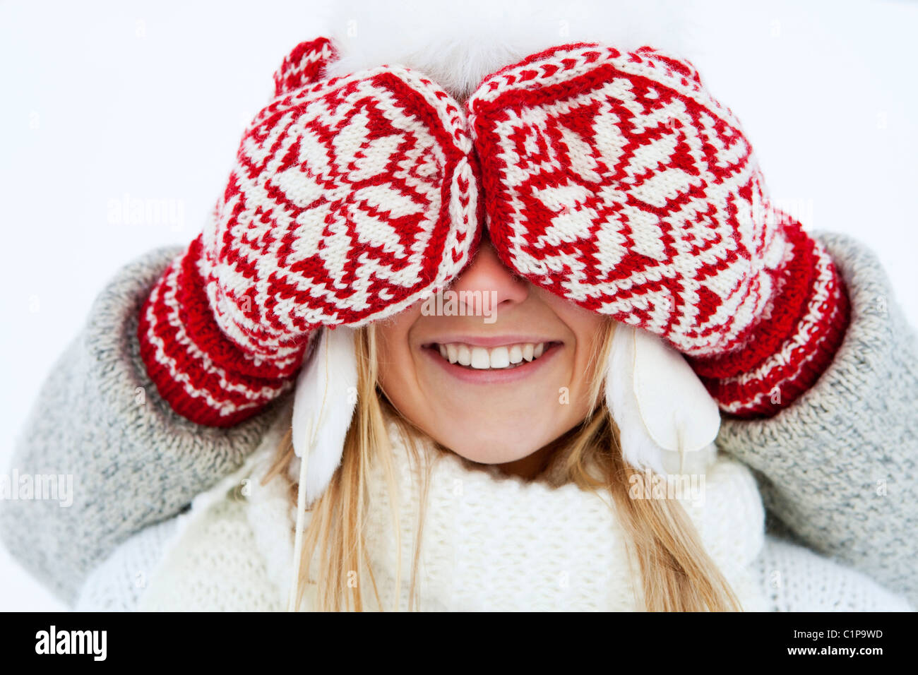 Girl having eyes covered by person wearing gloves - Stock Image