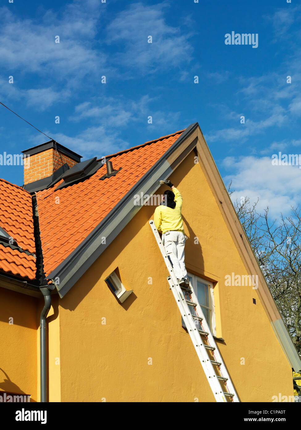 Man painting gable, low angle view - Stock Image