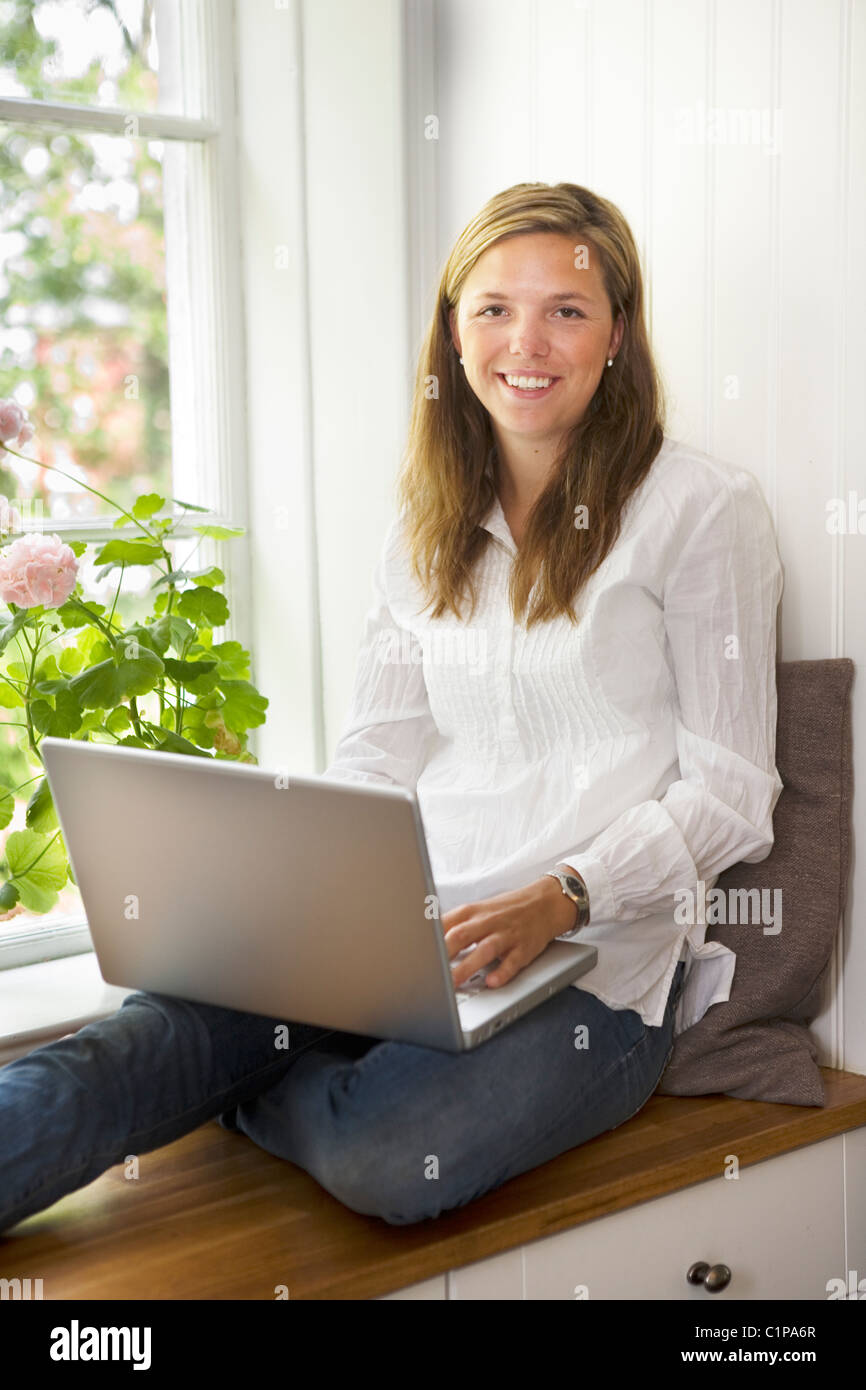 Portrait of young woman with laptop - Stock Image