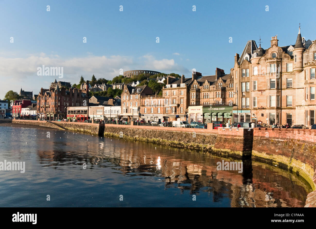 The sea frontage of Oban in early evening light with  McCaig's Folly in the background - Stock Image