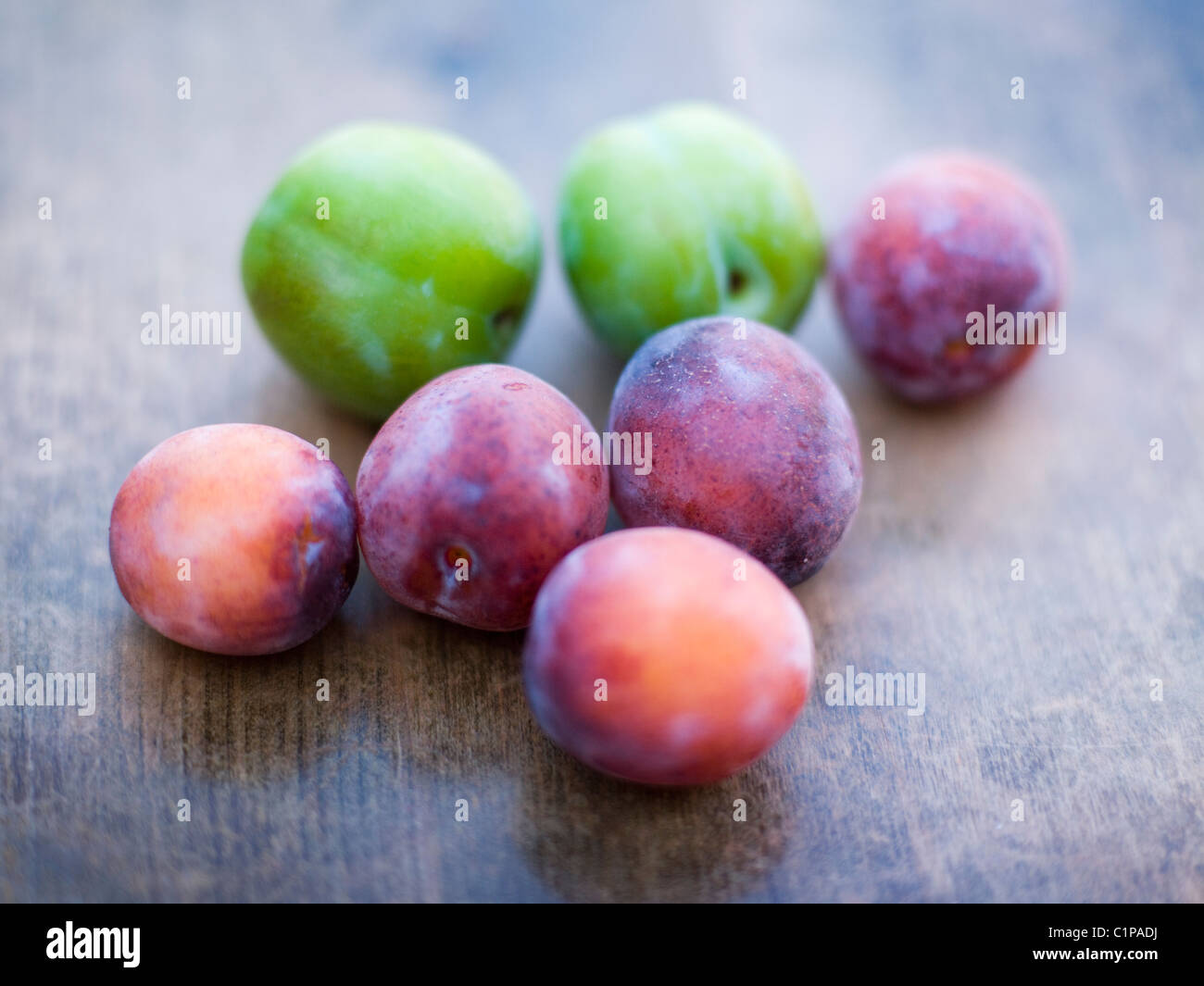 Green and purple plums on wooden table - Stock Image