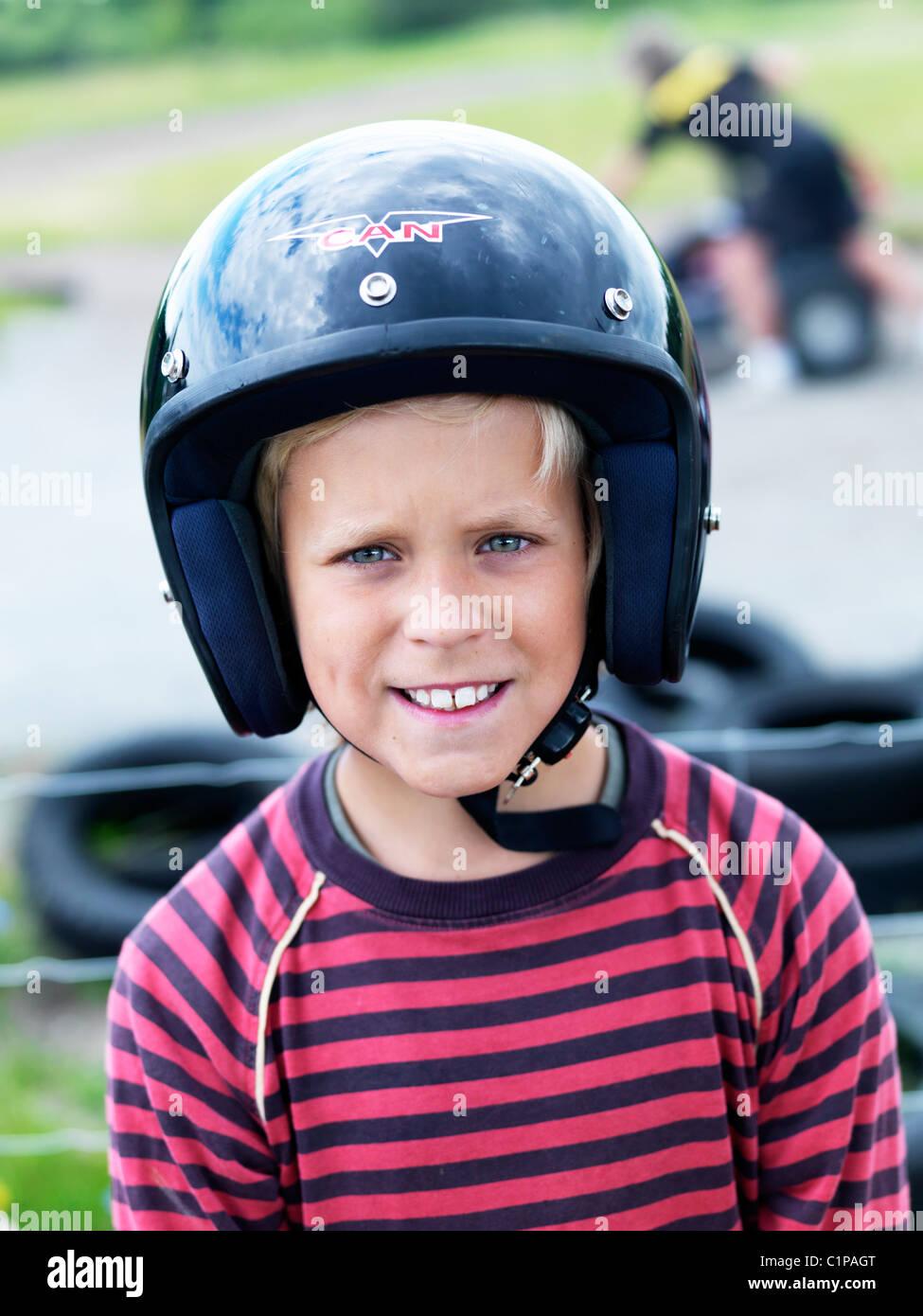 Portrait of boy wearing crash helmet at go-cart track Stock Photo