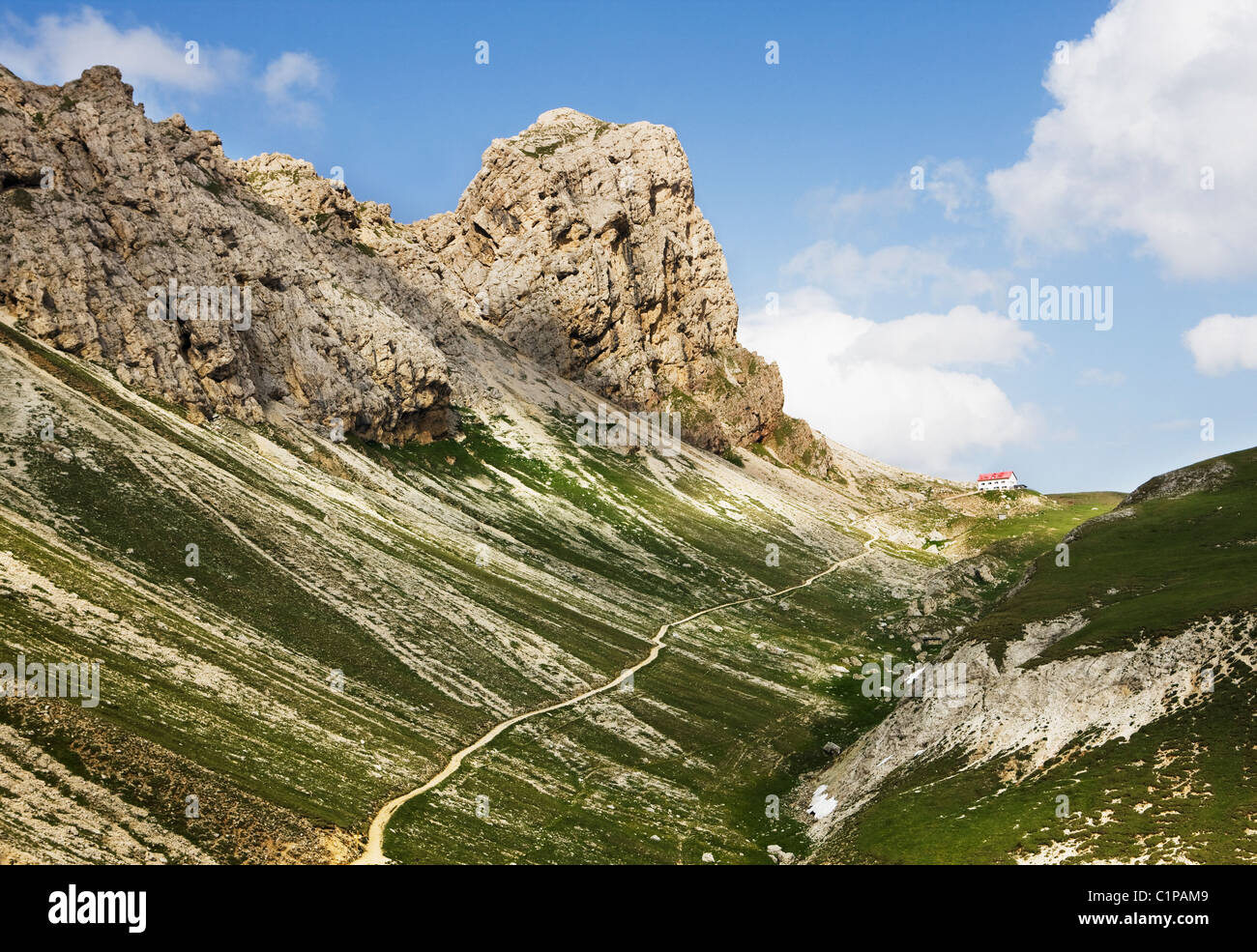 Tourist trail and remote mountain hostel in valley - Stock Image