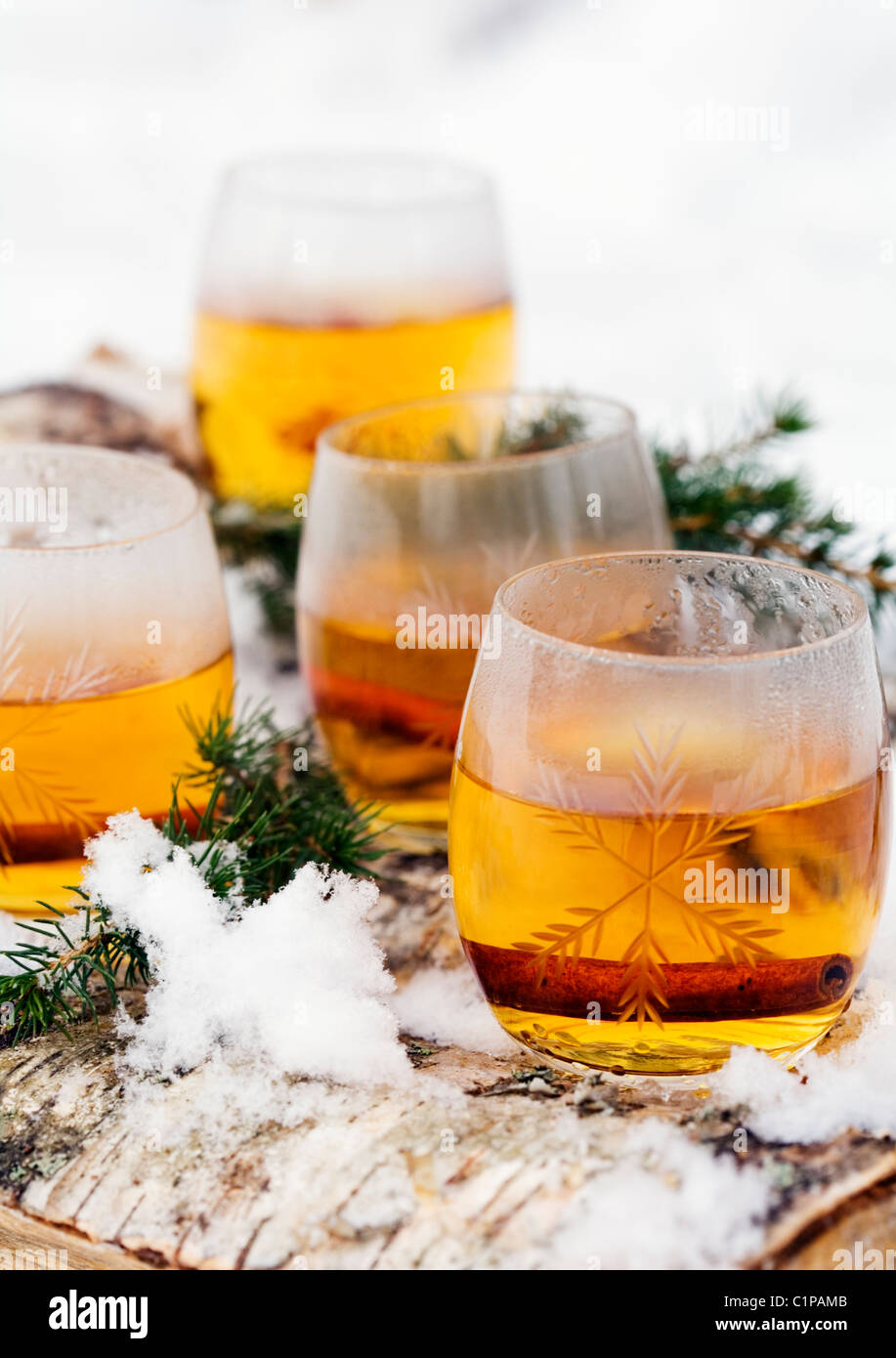 Glasses of mulled wine with spruce twigs and snow - Stock Image