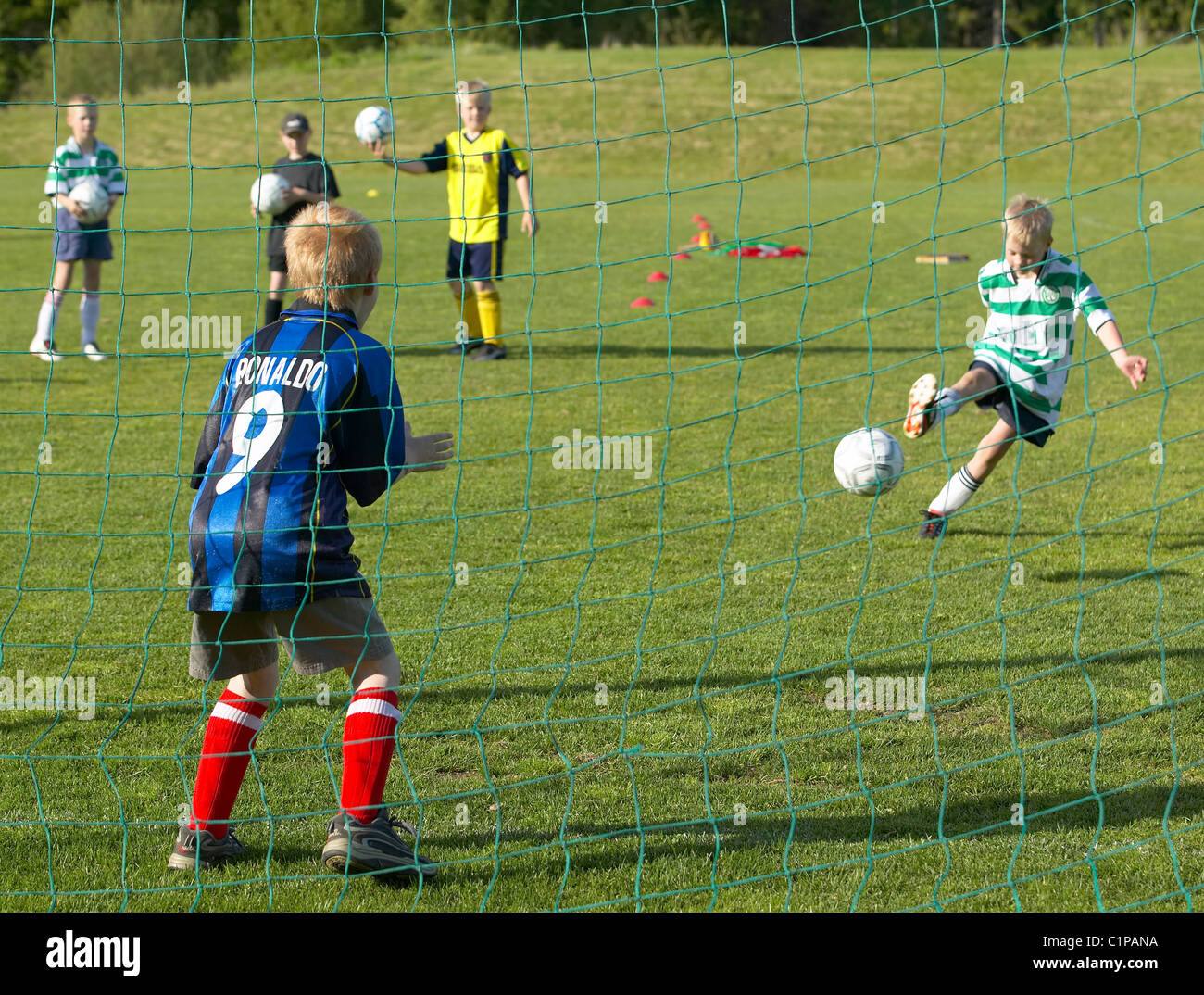 Boys playing soccer - Stock Image