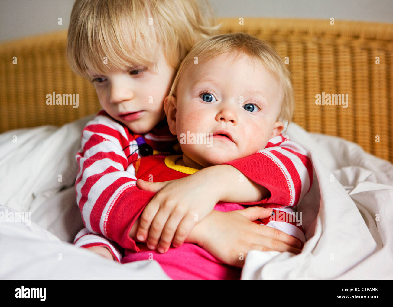 Boy embracing sister on bed - Stock Image
