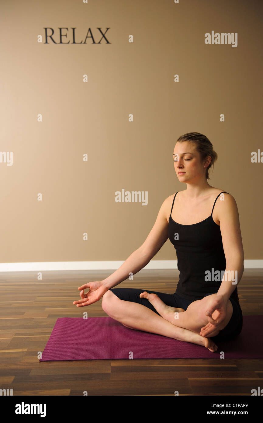 Woman sitting in lotus position - Stock Image