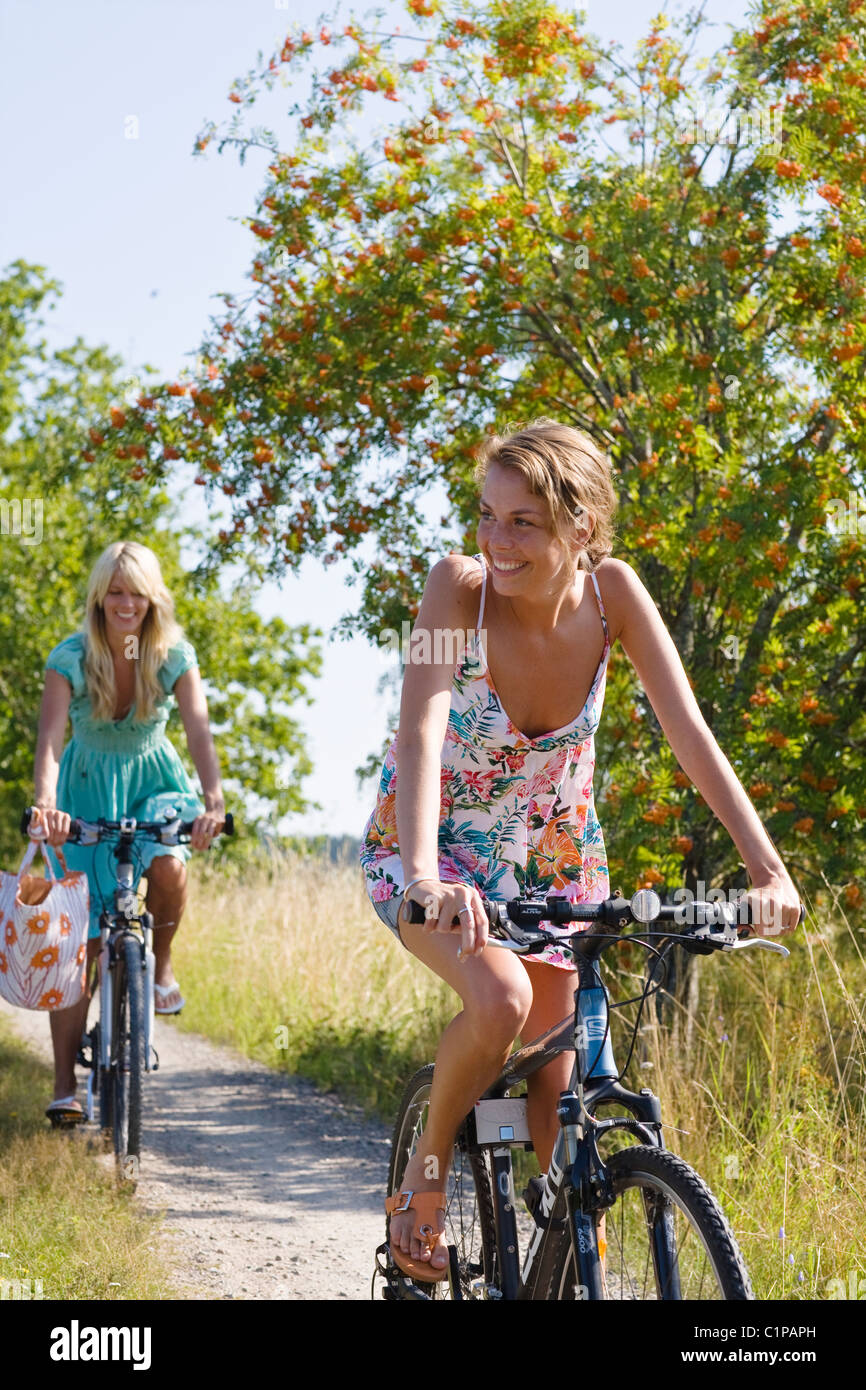 Two young women cycling - Stock Image
