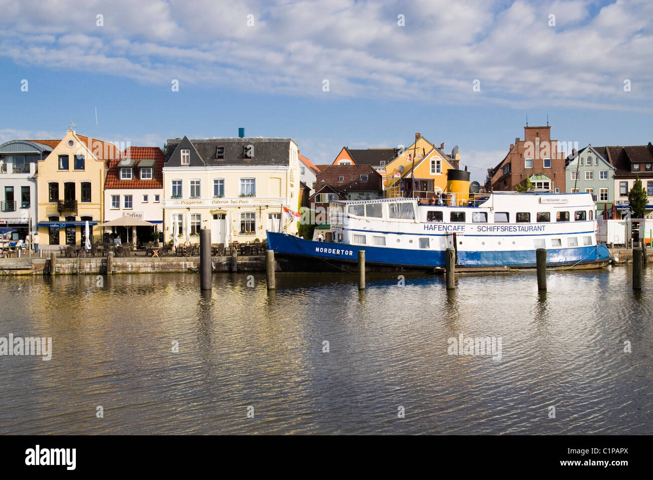 Germany, Husum, ferry in harbour lined with buildings - Stock Image