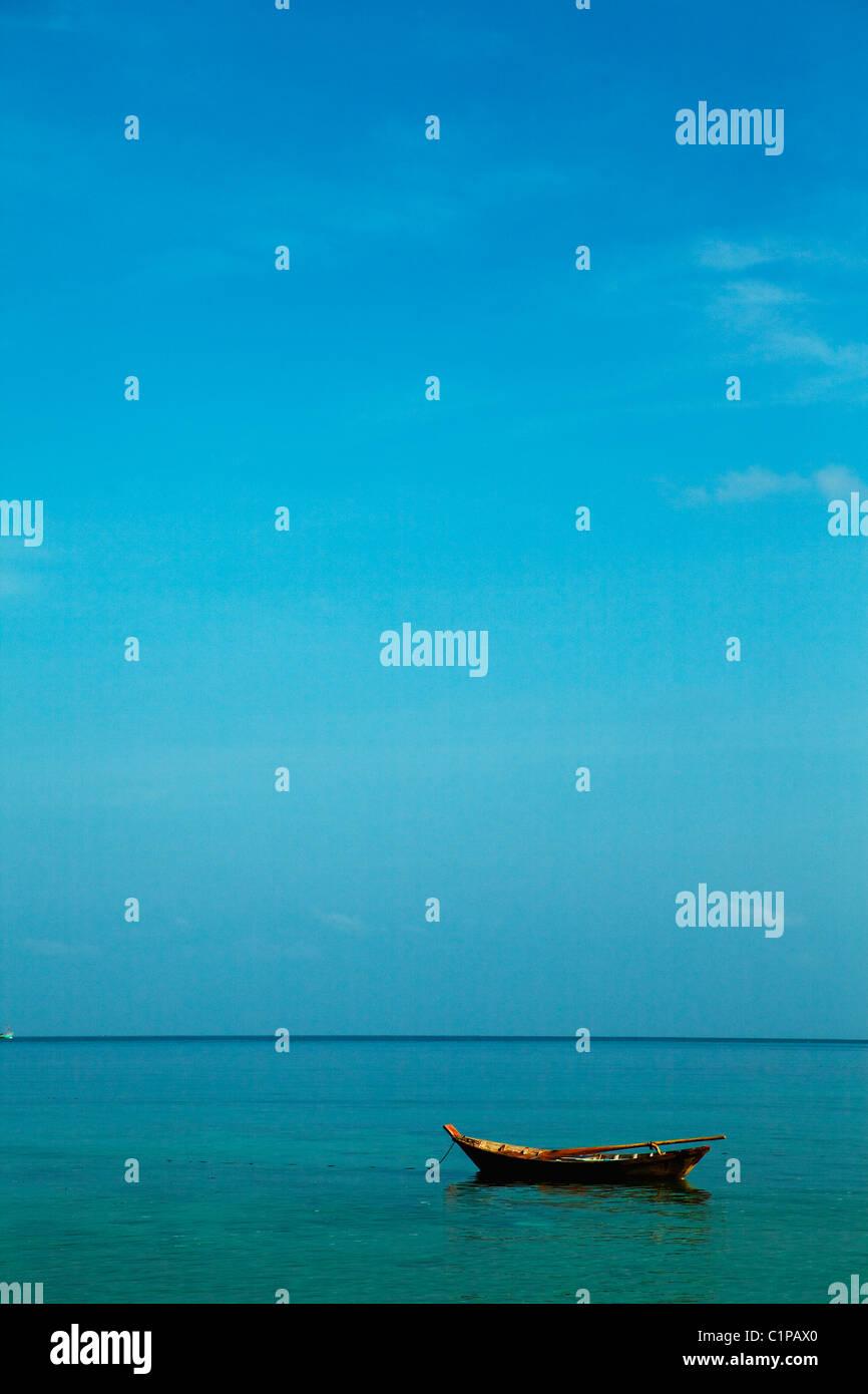 Rowboat on sea under blue sky - Stock Image