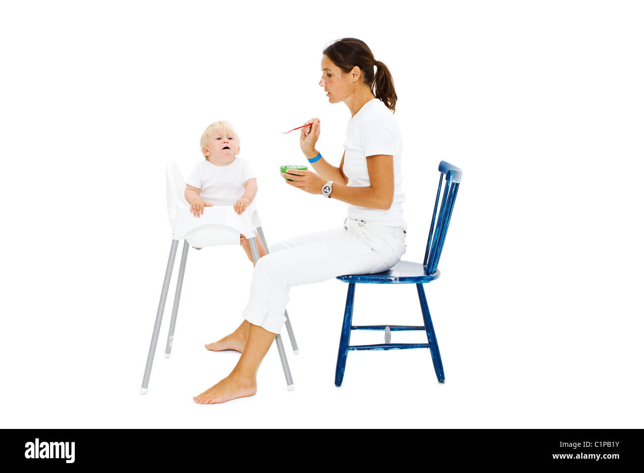 Boy in high chair being fed by mother - Stock Image