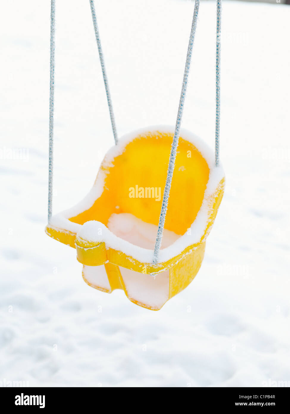 Plastic swing covered with snow - Stock Image