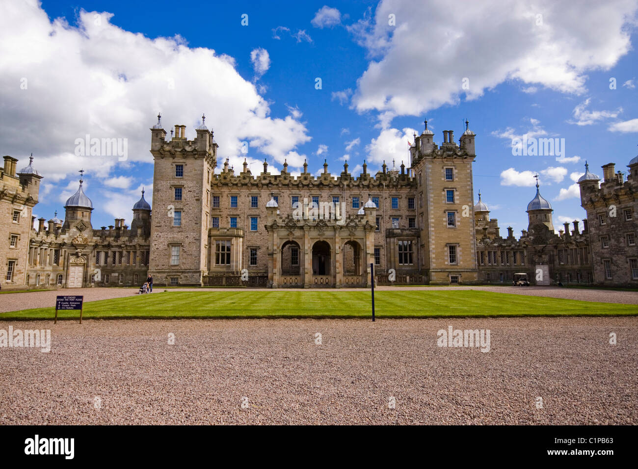 Scotland, Lothian and Borders, Floors Castle, facade of castle with lawn in foreground, blue sky and white clouds - Stock Image
