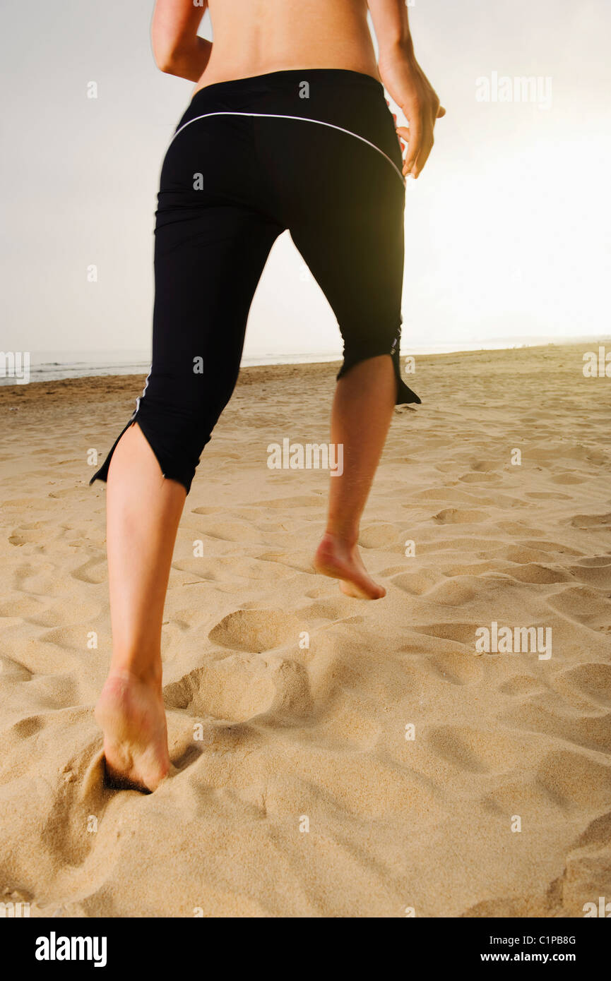 Woman jogging on beach - Stock Image