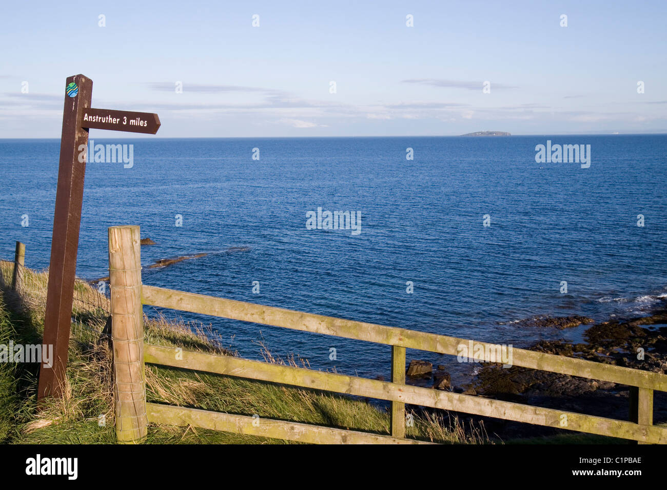 Scotland, Fife, Crail, signpost and fence overlooking sea - Stock Image