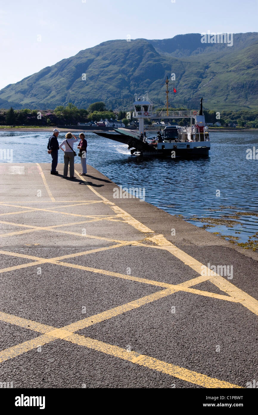 Scotland, Corran, people standing on jetty waiting for approaching ferry - Stock Image