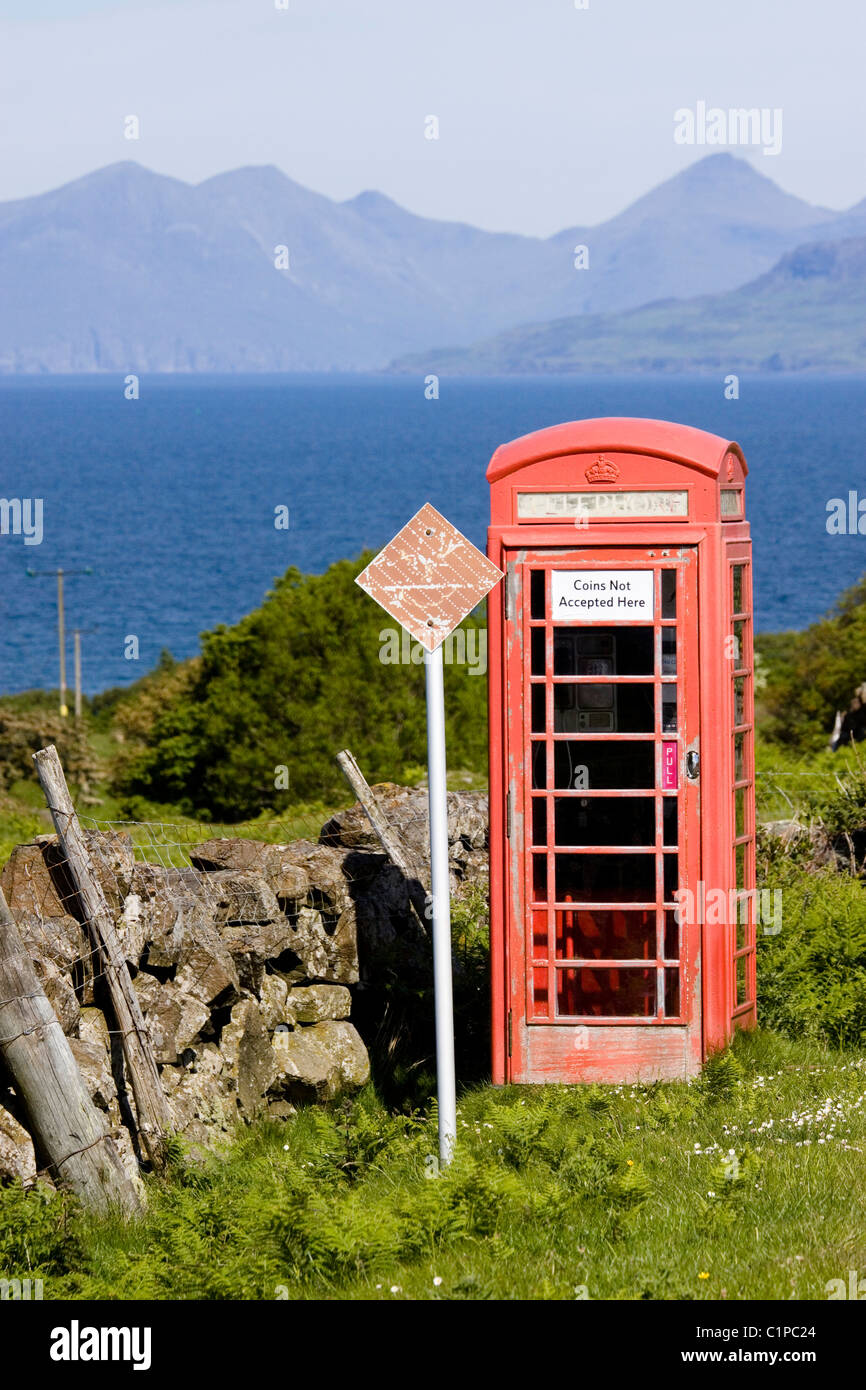 Scotland, Kilchoan, Ardnamurchan, red telephone box with sea and mountain range in background - Stock Image