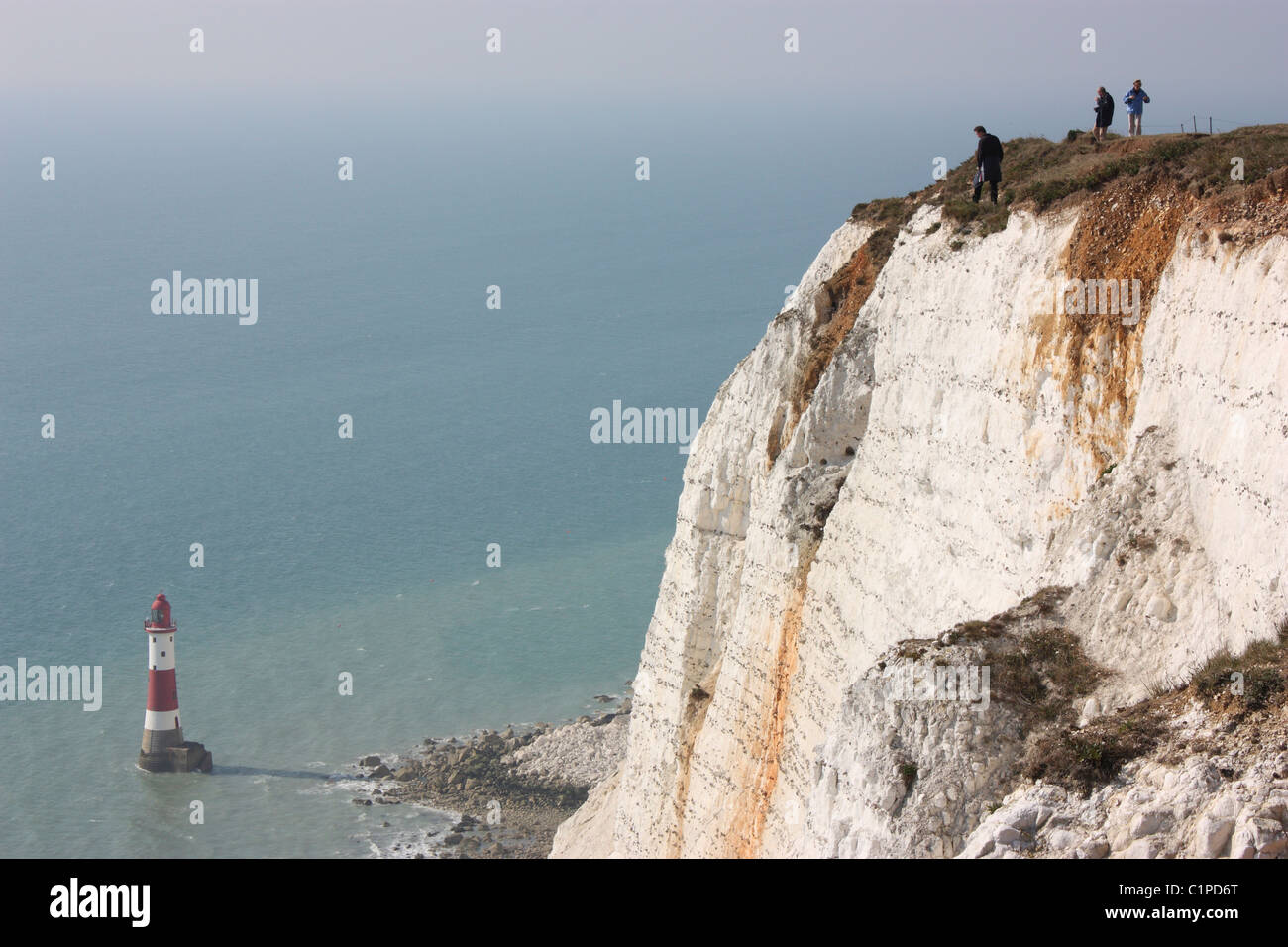 England, Beachy Head, people on top of white cliff with lighthouse below - Stock Image