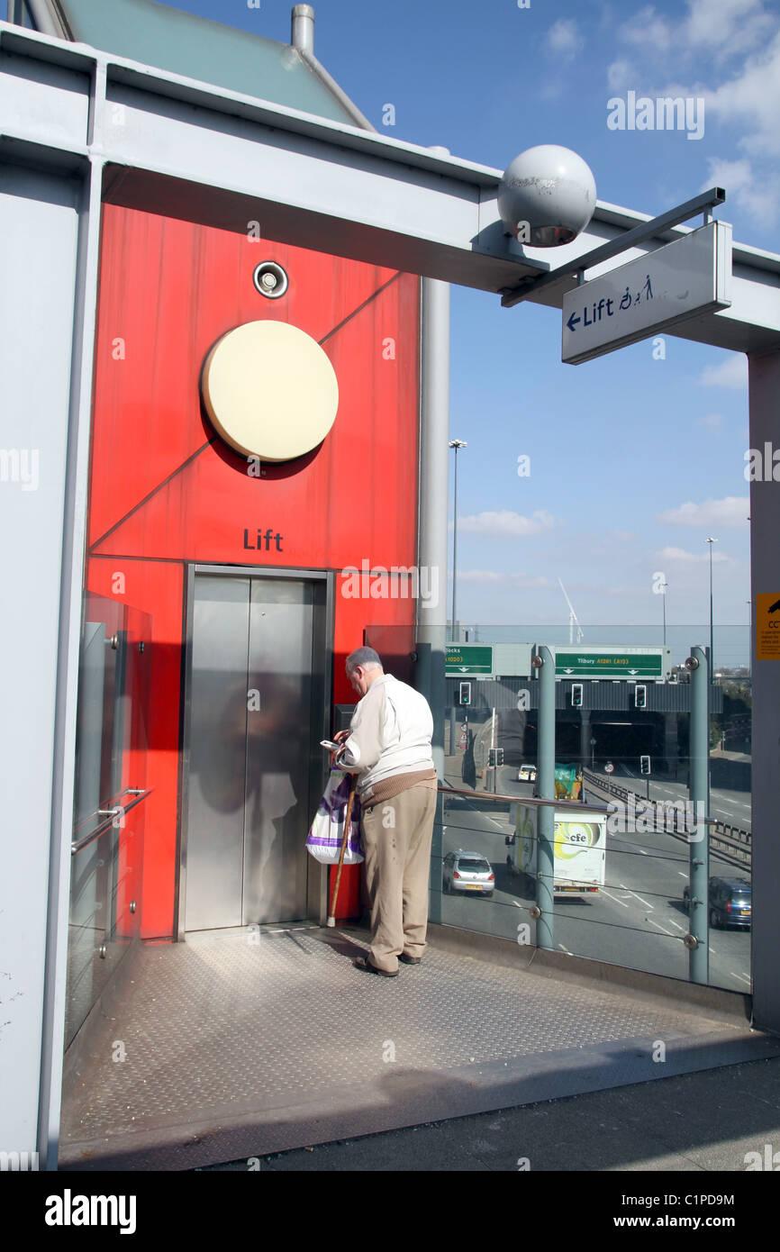 UK.PENSIONER USING LIFT ELEVATOR IN A FLYOVER BRIDGE OVER MOTORWAY  IN TOWER HAMLETS, LONDON - Stock Image