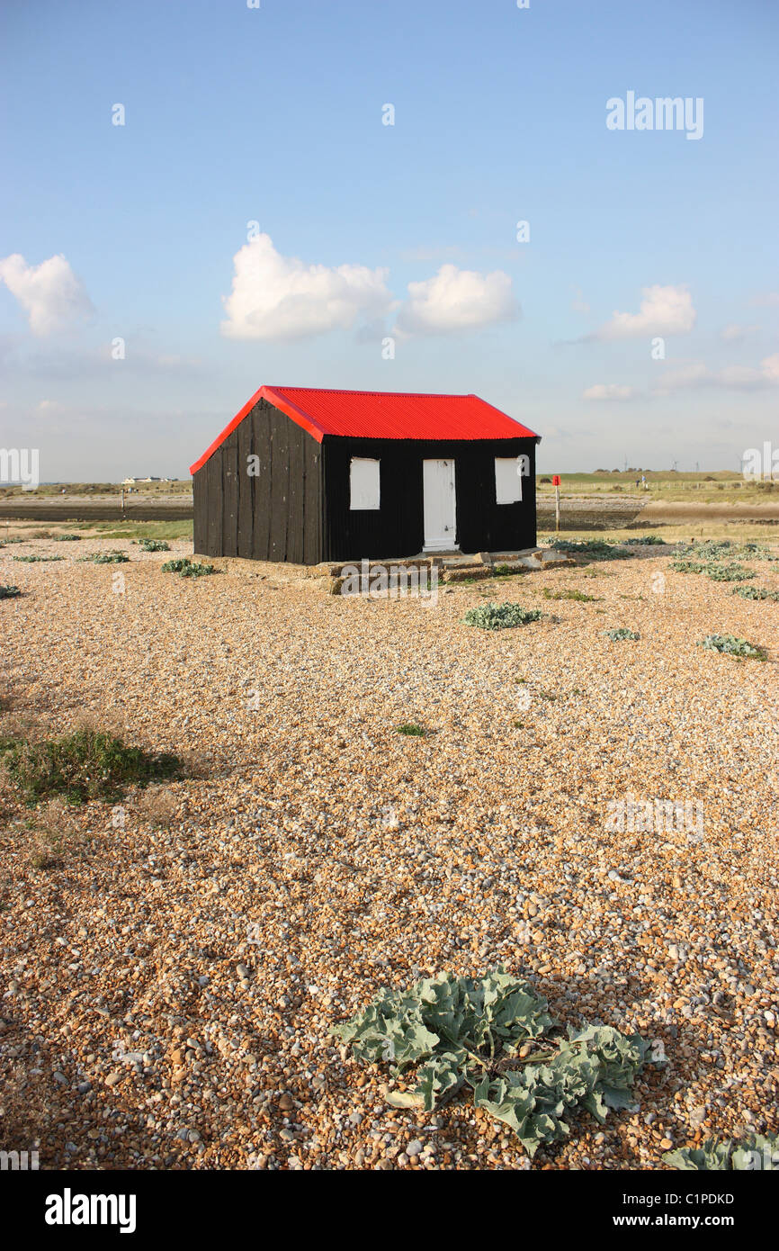 England, Sussex, Rye Harbour, red roof on wooden hut on shingle - Stock Image