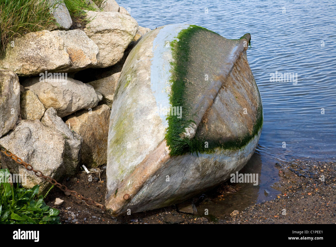 Republic of Ireland, Malahide, upside down fishing boat chained to rock - Stock Image