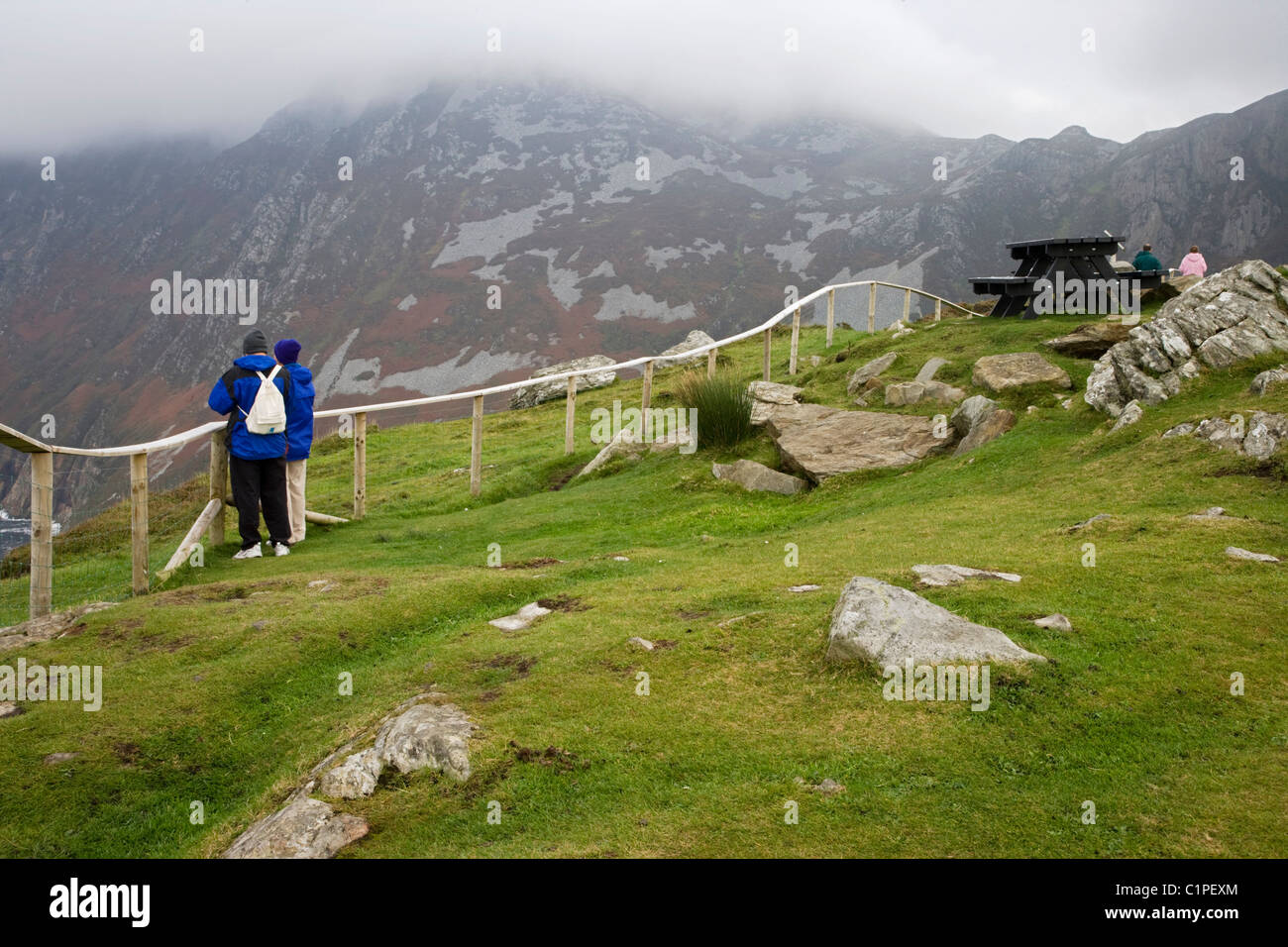 Republic of Ireland, County Donegal, Slieve League, people leaning on fence on clifftop - Stock Image