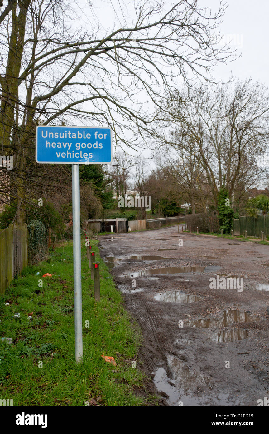 A sign reading 'Unsuitable for heavy goods vehicles' in front of a muddy, unmade road - Stock Image