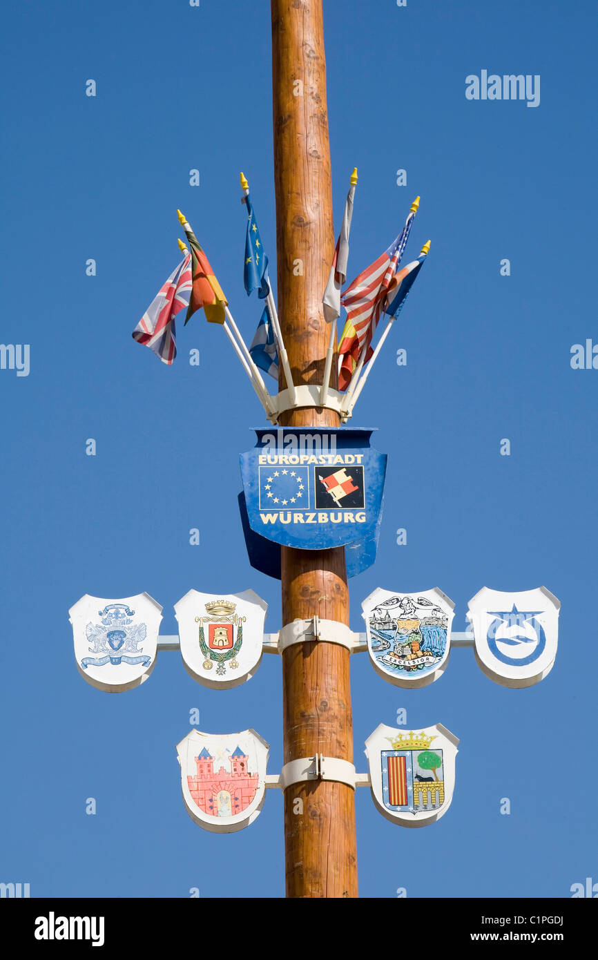 Germany, Bavaria, Wurzburg, Flags and symbol on wooden pole - Stock Image