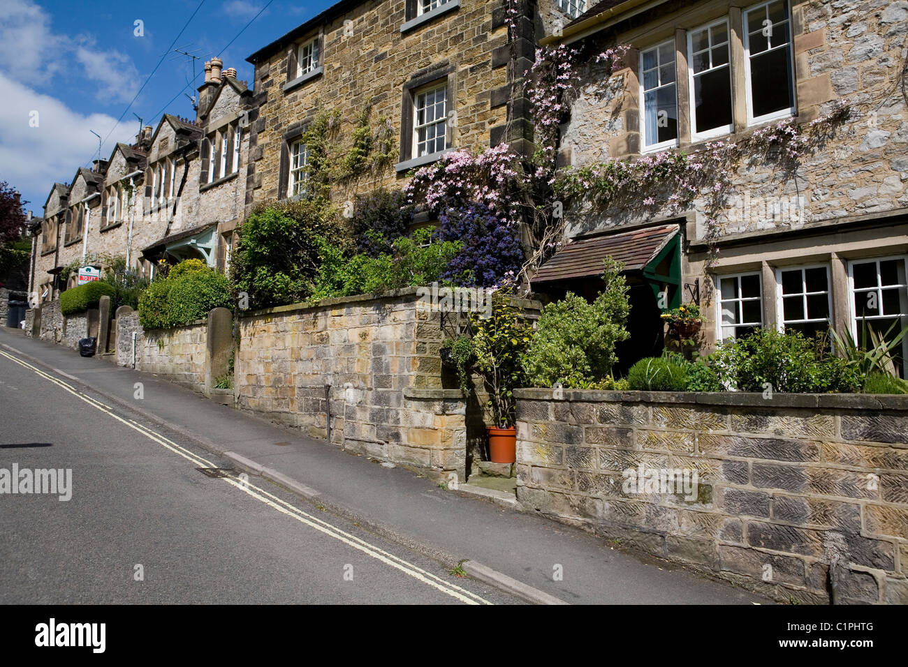 England, Derbyshire, Bakewell, terrace of stone houses on steep road - Stock Image
