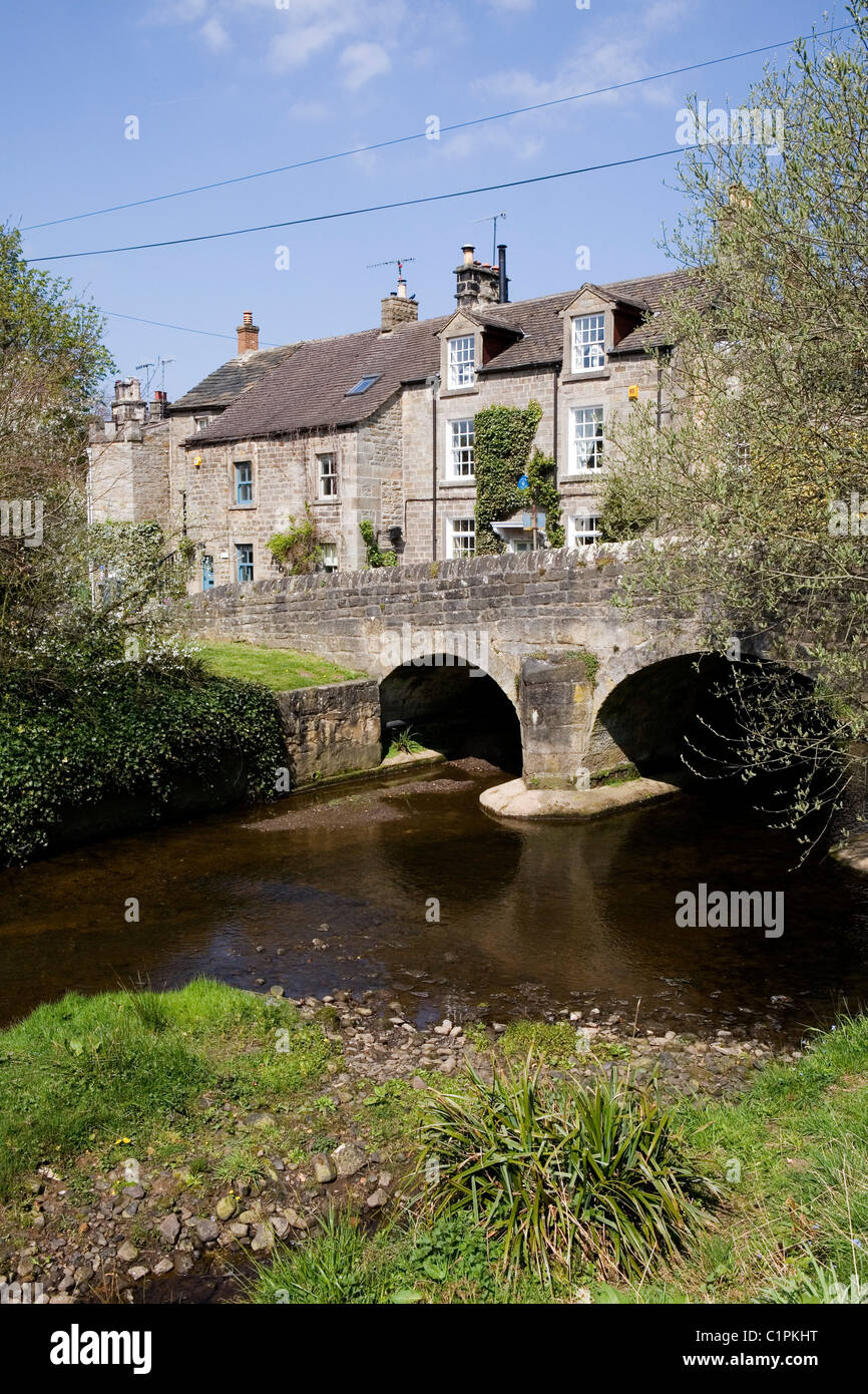 England, Derbyshire, Baslow, arch bridge over river with houses in background - Stock Image