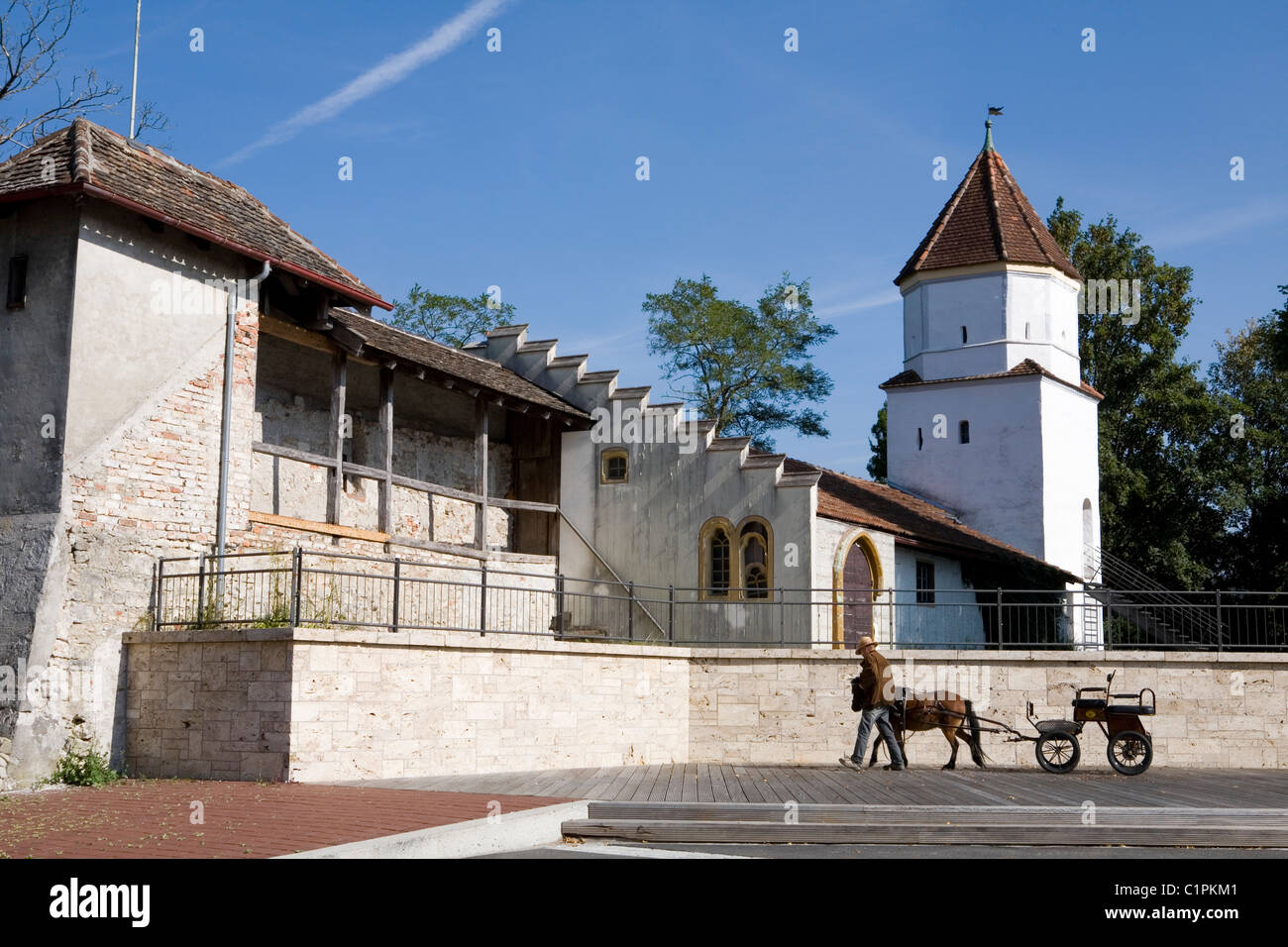 Germany, Bavaria, Schongau, man walking with horse and cart besides tower and old town walls - Stock Image