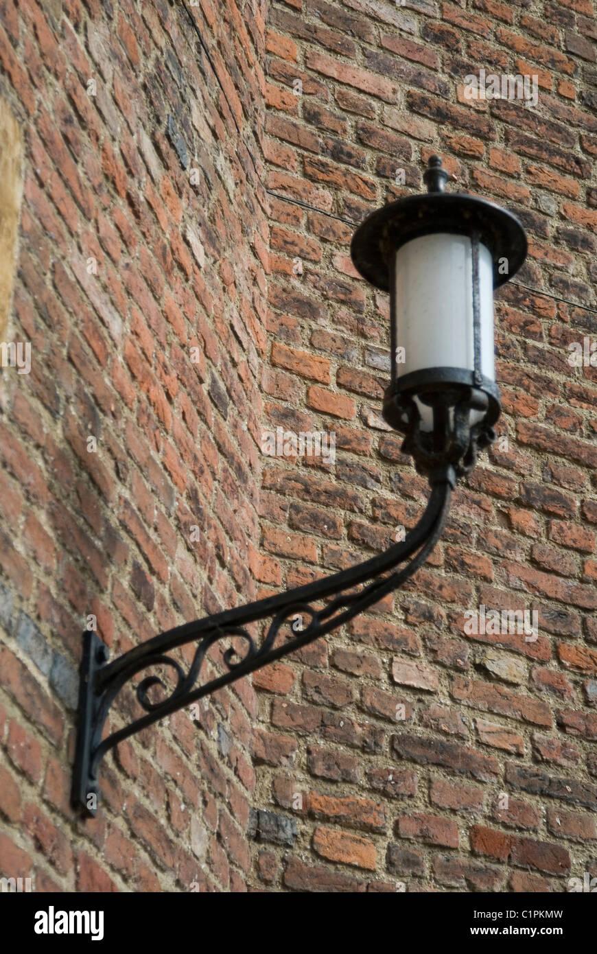 England, Cambridge, lamp on brick wall - Stock Image