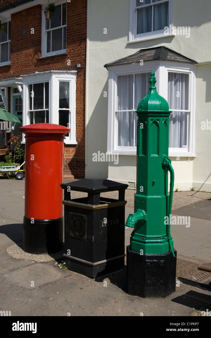 England, Essex, Thaxted, red letterbos, black litter bin, and green water pump - Stock Image
