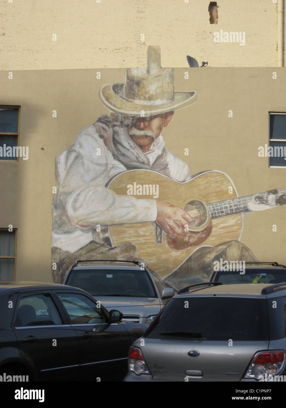 Large mural on wall of old cowboy playing a guitar, Denver, Colorado, USA. - Stock Image