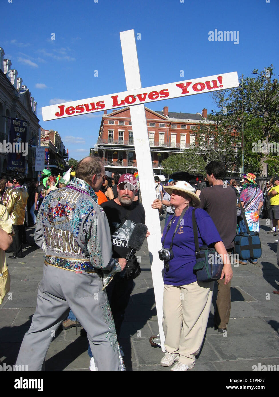Jesus Loves You. At the Mardi Gras festival, New Orleans, adult religious protestors interviewed by a man dressed - Stock Image