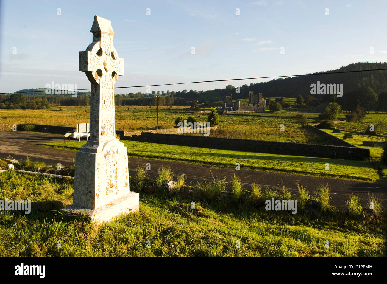 Republic of Ireland, Boyne Valley, Celtic Cross in graveyard of St Feichin's Church, Fore Abbey in distance. - Stock Image