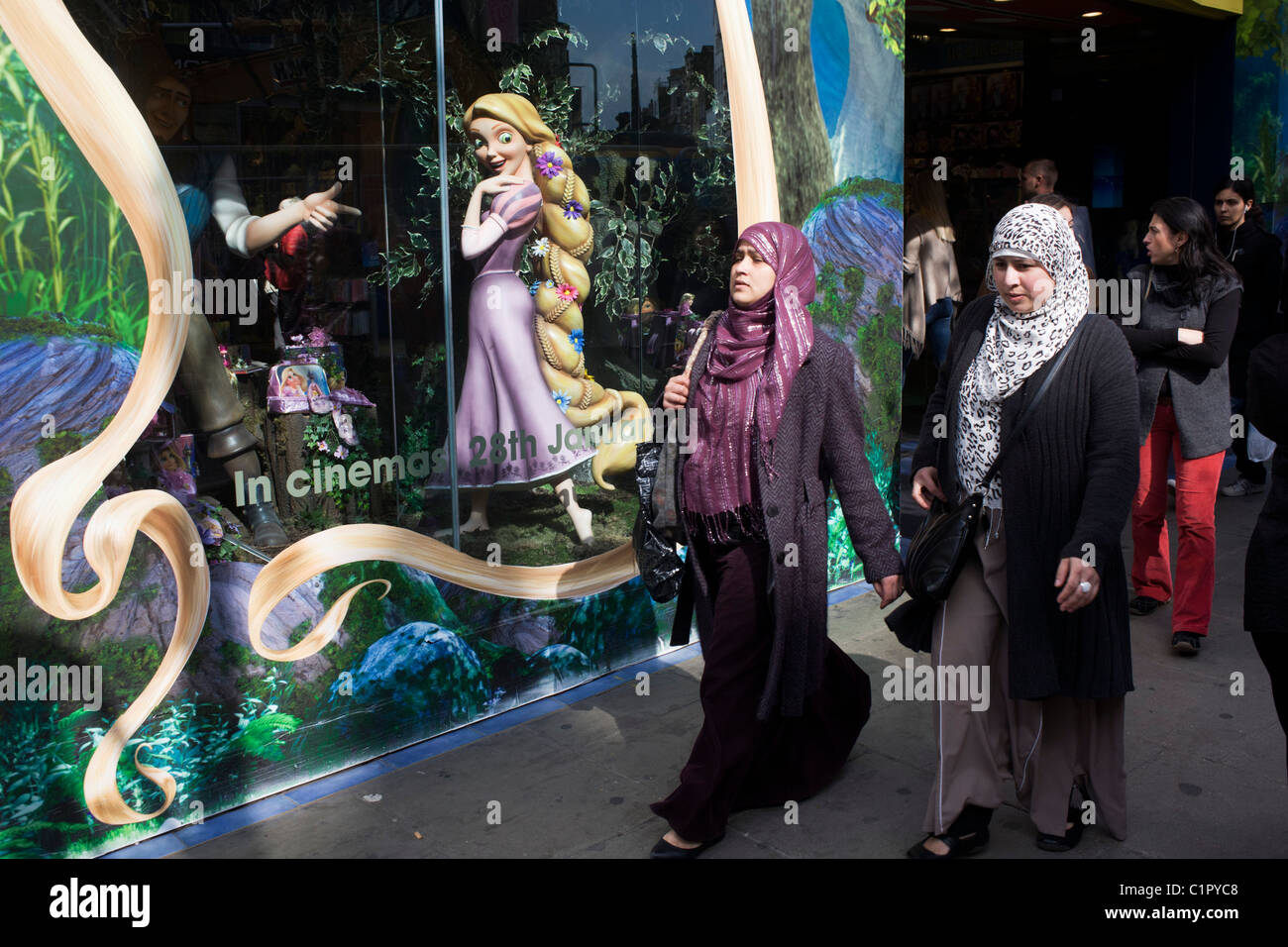Disney character Rapunzel from their film Tangled stands looking at Muslim women, exemplifying feminine beauty. Stock Photo