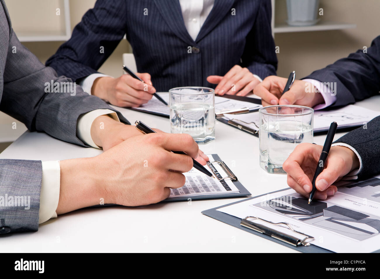 Close-up of workteam reading documents at business meeting - Stock Image