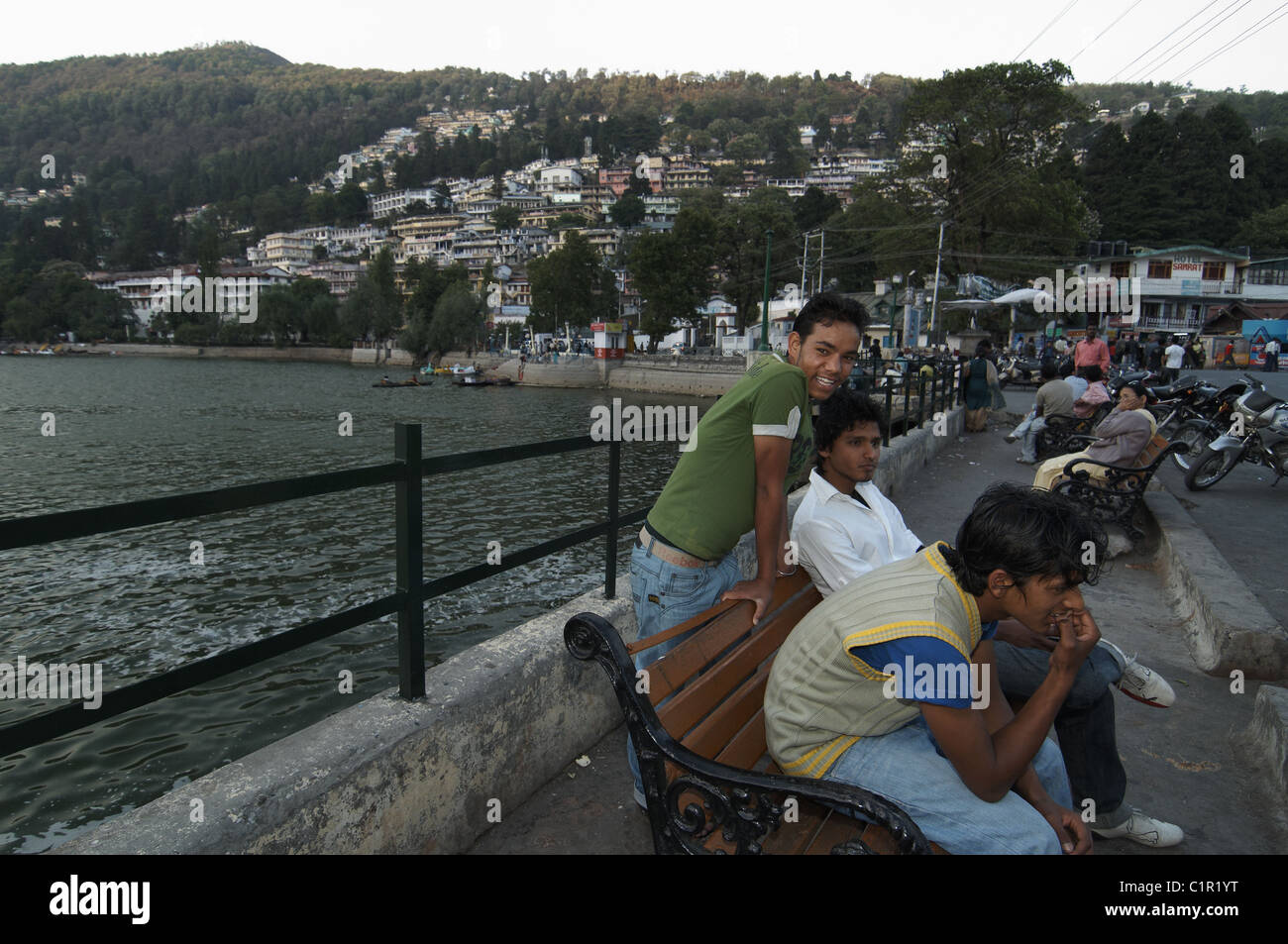 Young people relaxing in by the lake in the mountain village of Nainital in the Himalayan foothills of India - Stock Image