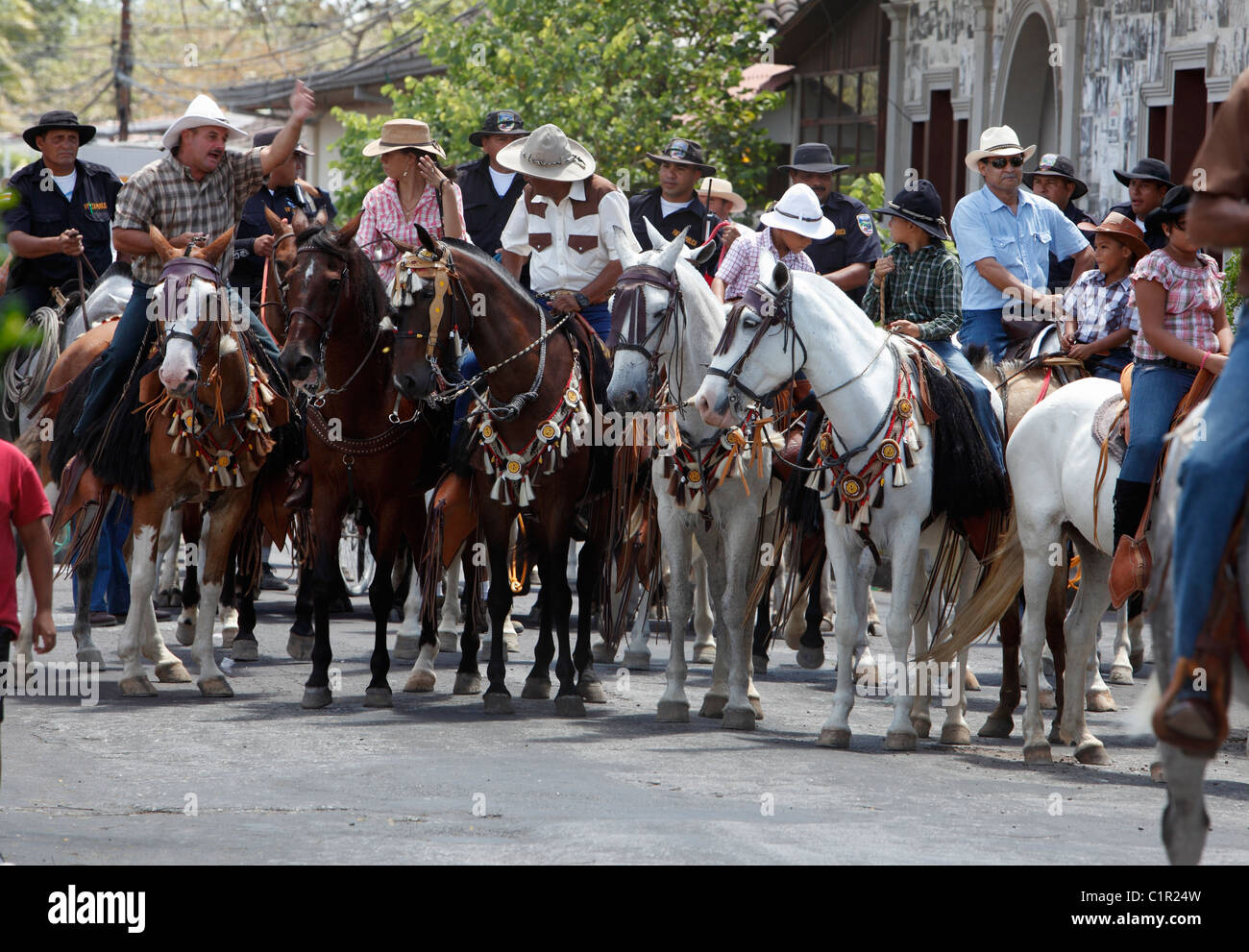 Men and women riding horses in the civic festival horse parade in Liberia, Costa Rica - Stock Image