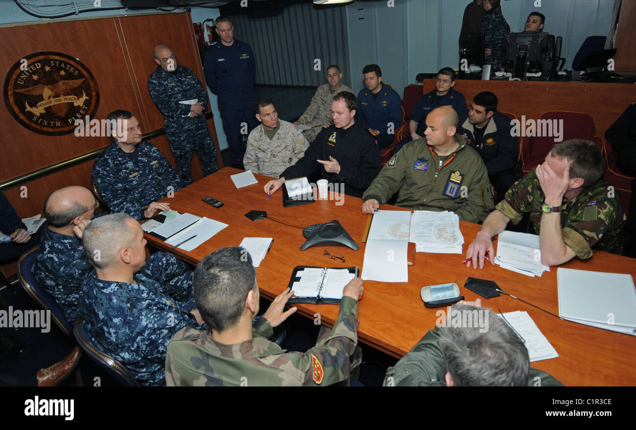Liaison officers from coalition countries meet with Joint Task Force Odyssey Dawn staff members aboard the amphibious - Stock Image