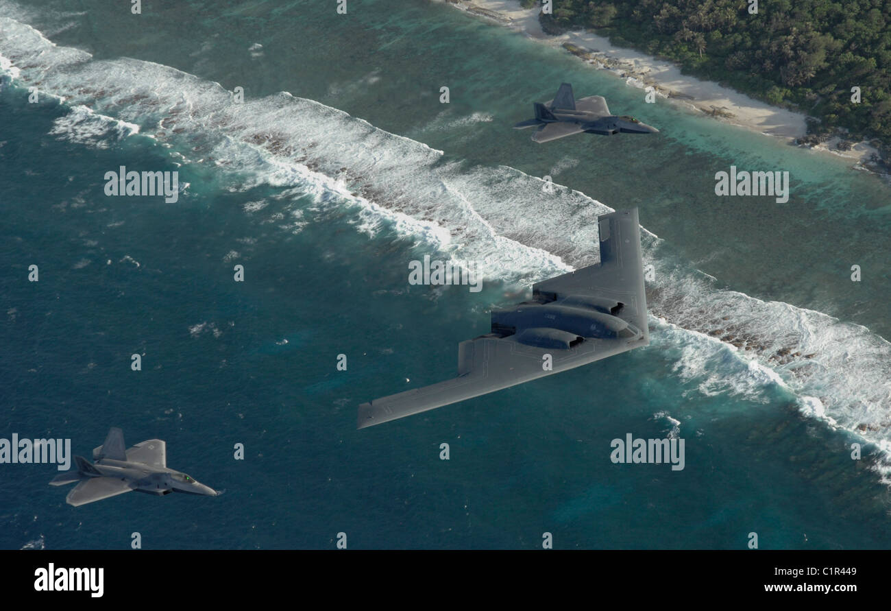 Two F-22 Raptors and a B-2 Spirit bomber deployed to Andersen Air Force Base, Guam, fly in formation over the Pacific - Stock Image
