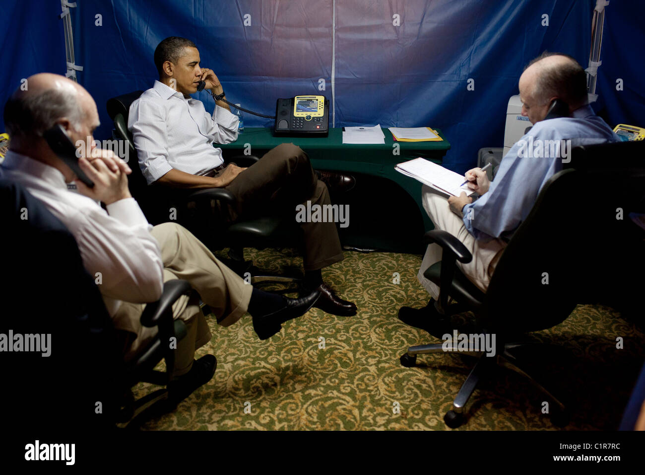 President Barack Obama is briefed on the situation in Libya during a secure conference call. - Stock Image