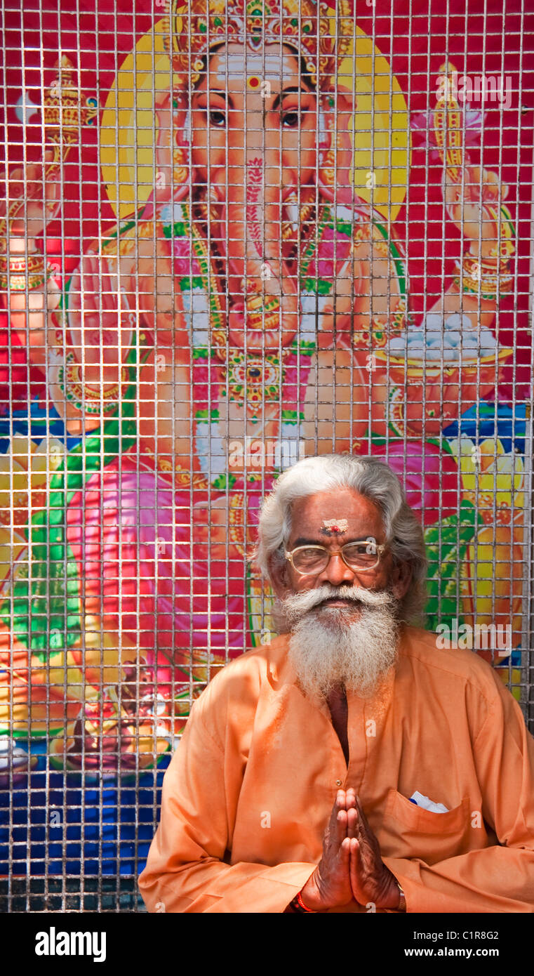 Sadhu or holy man in front of poster of Hindu god Ganesh in Kerala's capital of Trivandrum. Stock Photo