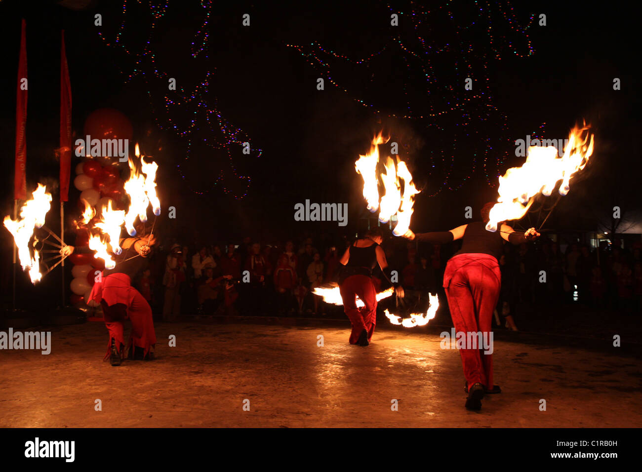 Female firedancing troupe perform at an outdoor night time celebration - Stock Image