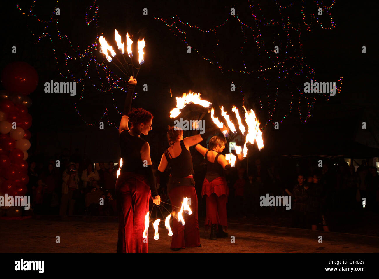 Graceful and artistic female firedancing troupe perform at an outdoor night time celebration - Stock Image