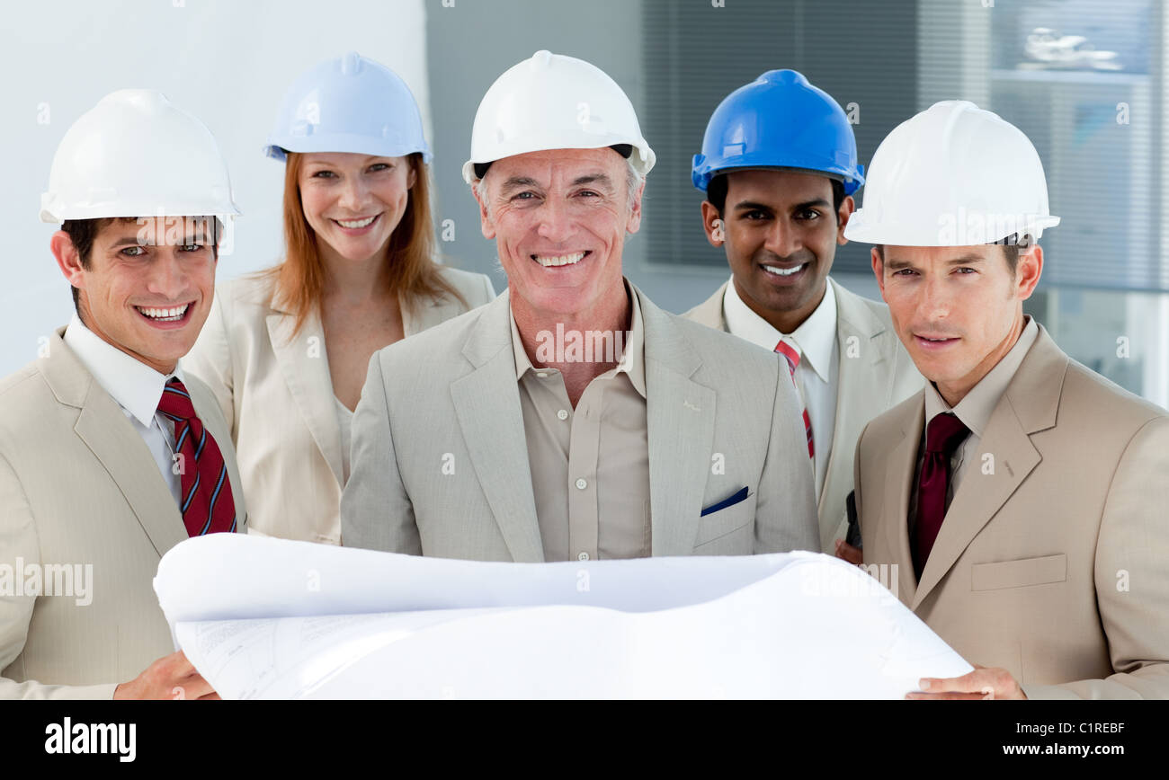 Architects with hardhats in a building site - Stock Image